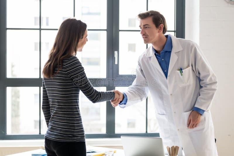 Medico affidabile e paziente femminile che stringono le mani prima della consultazione fotografia stock