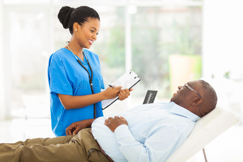 Medico africano che consulta paziente senior fotografia stock