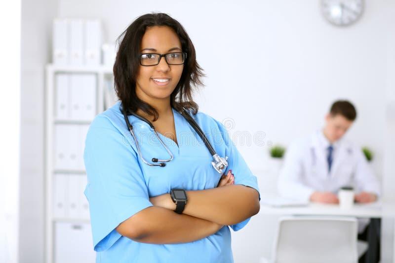 Medico afroamericano femminile con i colleghi nel fondo fotografia stock libera da diritti