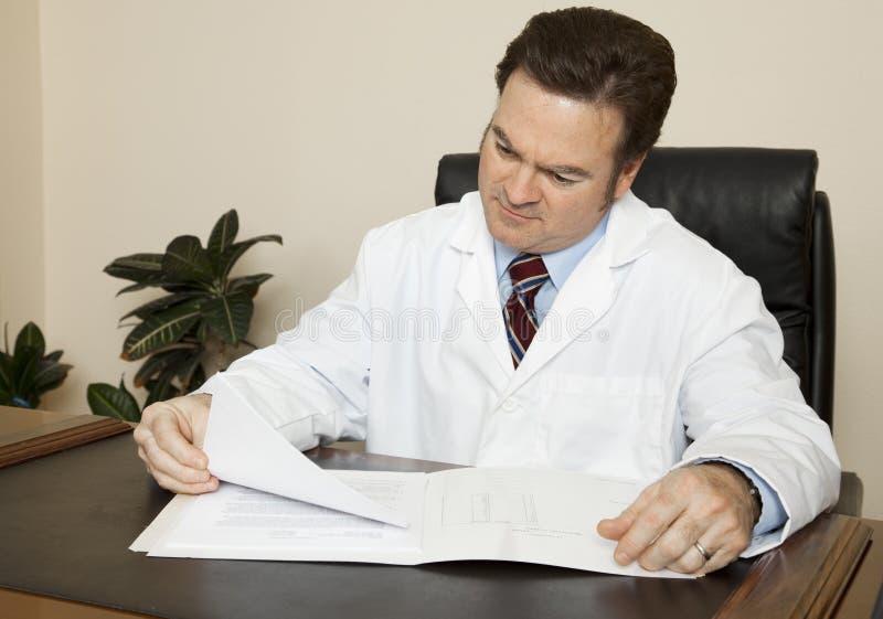 Medico al suo scrittorio immagine stock libera da diritti