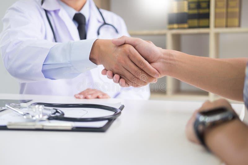 Medico alla clinica che dà una stretta di mano al suo paziente per il enco immagini stock
