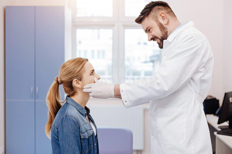 Medico allegro bello che esamina il suo paziente immagini stock libere da diritti