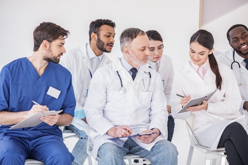Medico allegro che dice con i partner in clinica fotografia stock libera da diritti