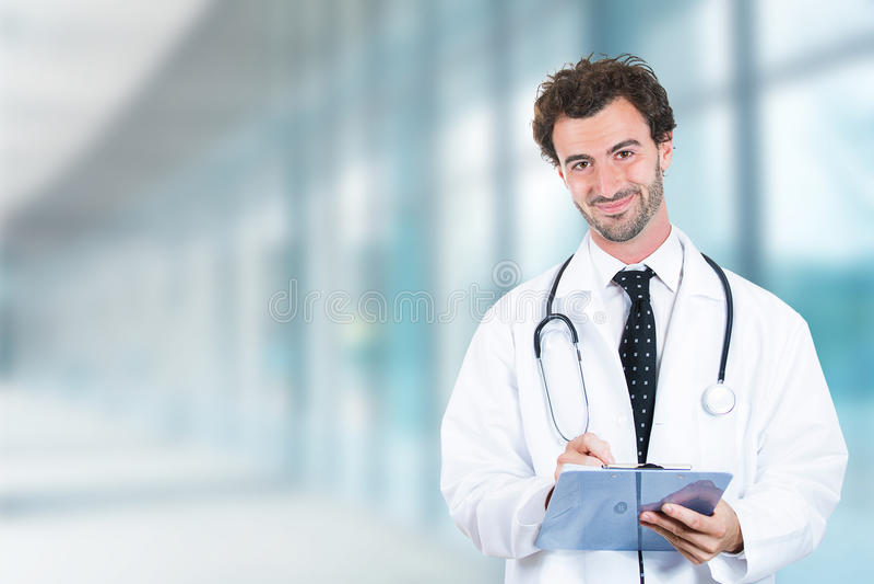 Medico amichevole con stare sorridente della lavagna per appunti nel corridoio dell'ospedale fotografie stock libere da diritti