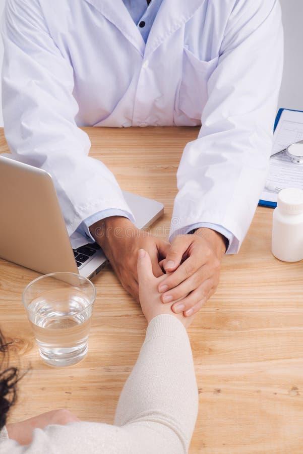 Medico amichevole passa a tenuta la mano paziente che si siede allo scrittorio f fotografia stock libera da diritti