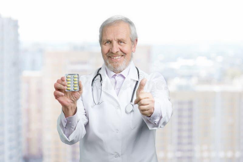 Medico anziano con le pillole ed il pollice su immagine stock libera da diritti