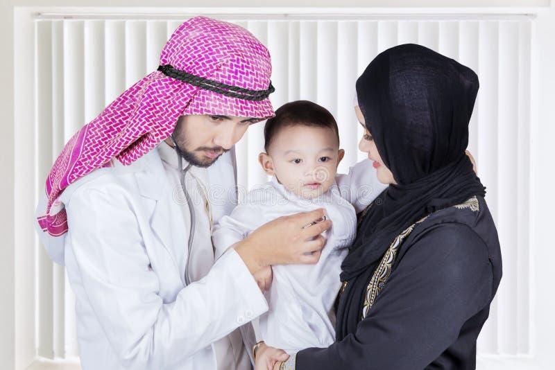 Medico arabo che esamina un ragazzino fotografia stock