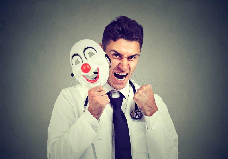 Medico arrabbiato che decolla maschera sorridente fotografia stock libera da diritti