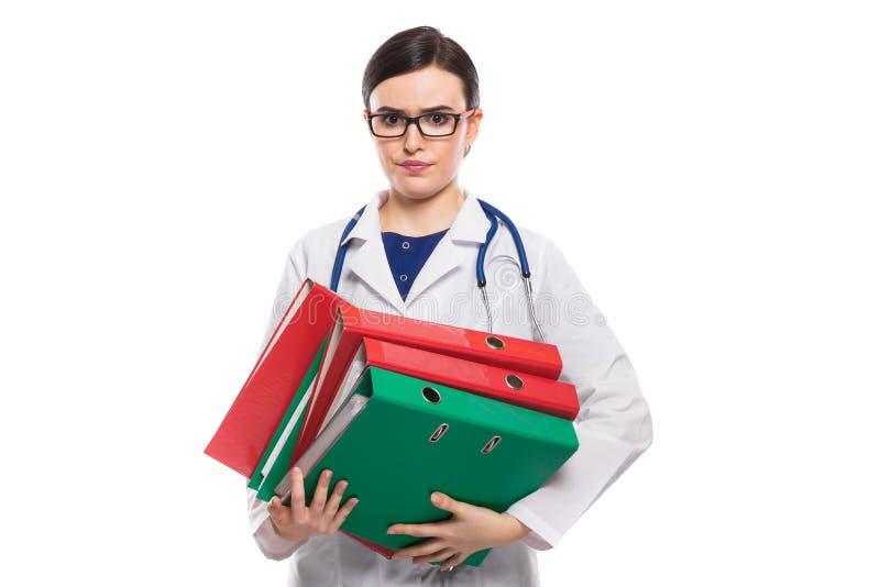 Medico arrabbiato della giovane donna con i raccoglitori della tenuta dello stetoscopio in sue mani in uniforme di bianco su fond immagini stock libere da diritti