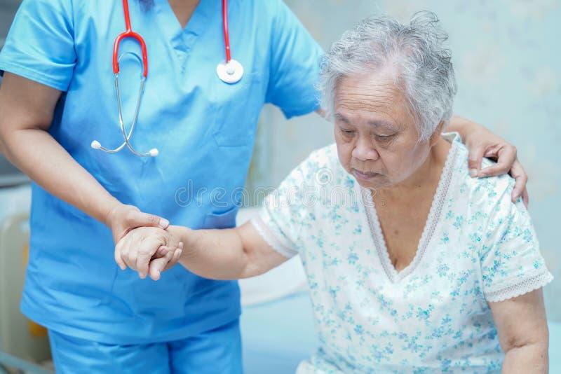 Medico asiatico del fisioterapista dell'infermiere preoccuparsi, aiutare e sostenere il paziente anziano della donna della signor immagine stock libera da diritti