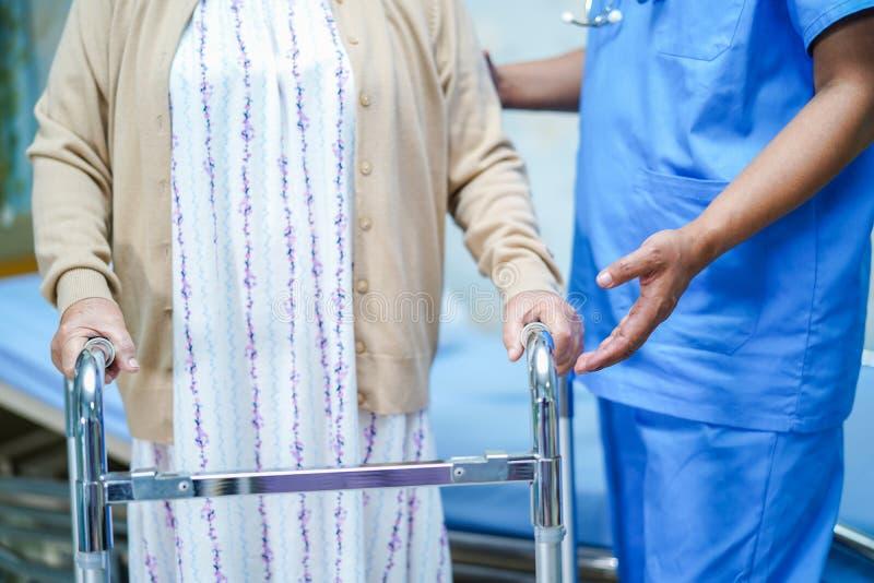Medico asiatico del fisioterapista dell'infermiere preoccuparsi, aiutare e sostenere il paziente senior o anziano della donna del fotografie stock libere da diritti