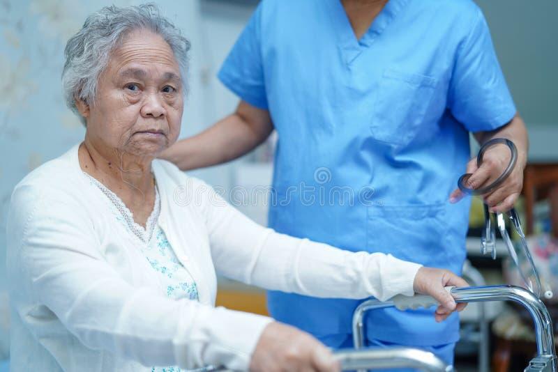 Medico asiatico del fisioterapista dell'infermiere preoccuparsi, aiutare e sostenere il paziente senior o anziano della donna del immagini stock