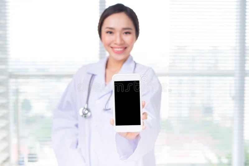 Medico asiatico della donna che mostra uno schermo dello smartphone immagine stock