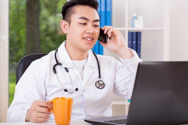 Medico asiatico durante irrompe l'ufficio immagini stock libere da diritti