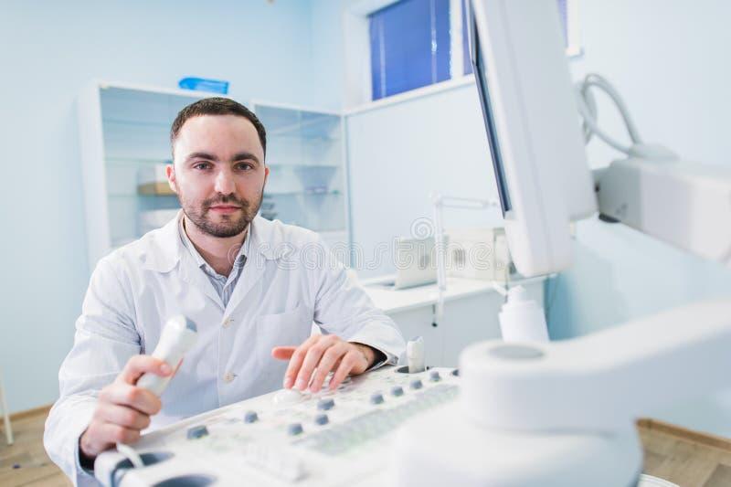 Medico bello che per mezzo di una macchina di ultrasuono fotografie stock