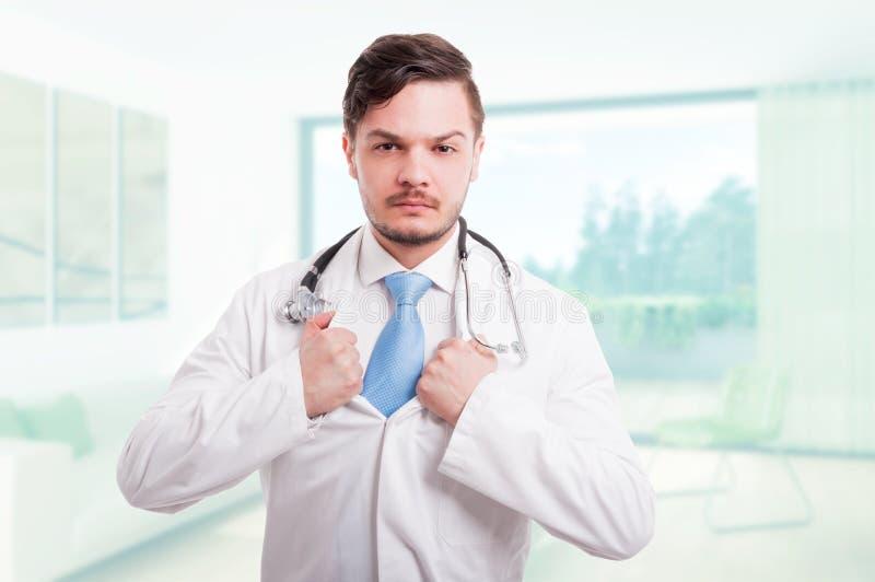 Medico bello che strappa il suo cappotto del laboratorio fotografia stock libera da diritti