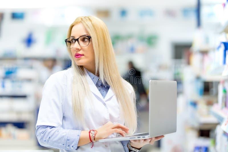 Medico biondo, giovane farmacista che cerca i farmaci da vendere su ricetta medica sul computer portatile Donna della farmacia ch immagini stock