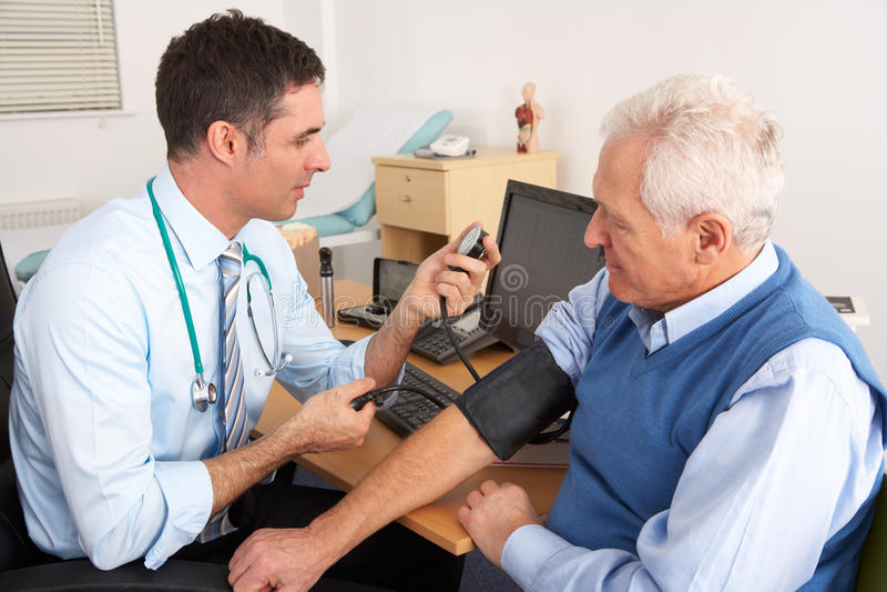 Medico britannico che cattura pressione sanguigna dell'uomo maggiore immagine stock libera da diritti