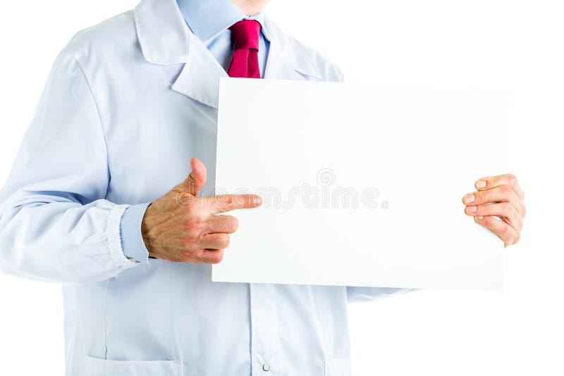 Medico in camice che mostrano un'insegna in bianco bianca immagini stock