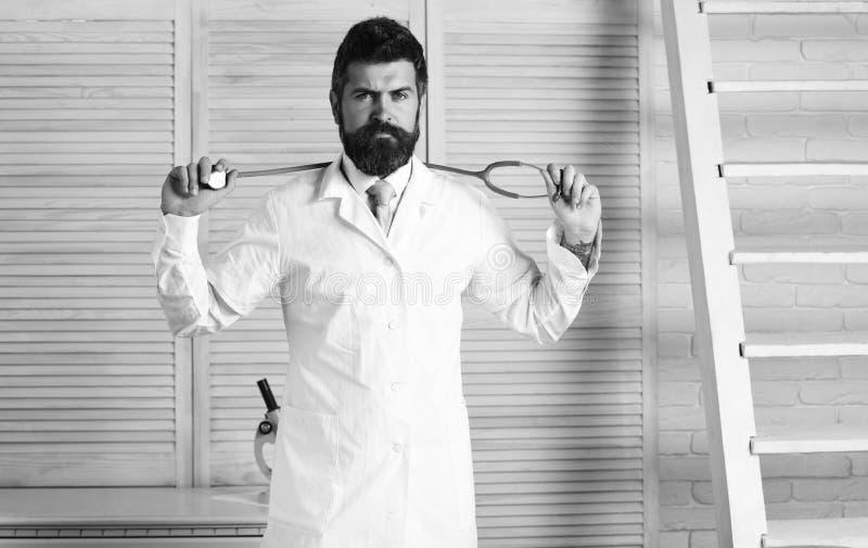 Medico in cappotto medico bianco tiene l'attrezzatura Uomo in uniforme chirurgica con lo stetoscopio sul collo fotografie stock