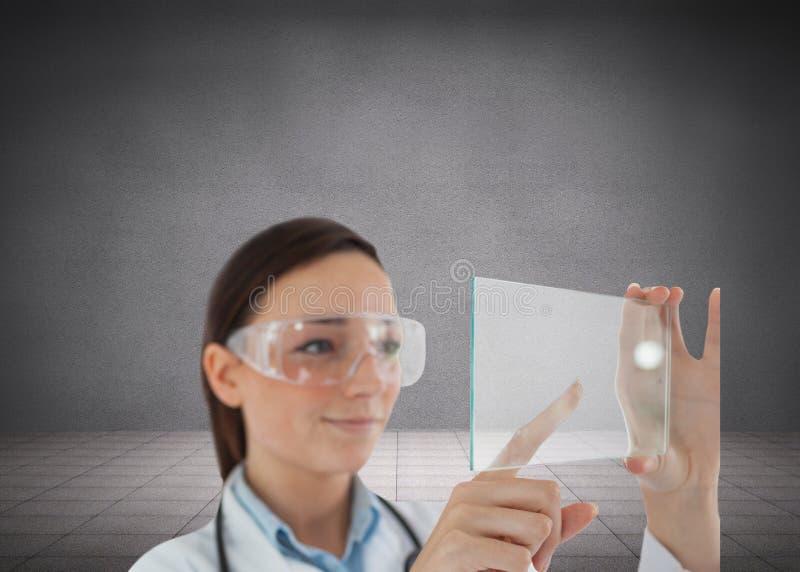 Medico castana in vetri di protezione che tengono schermo virtuale fotografia stock