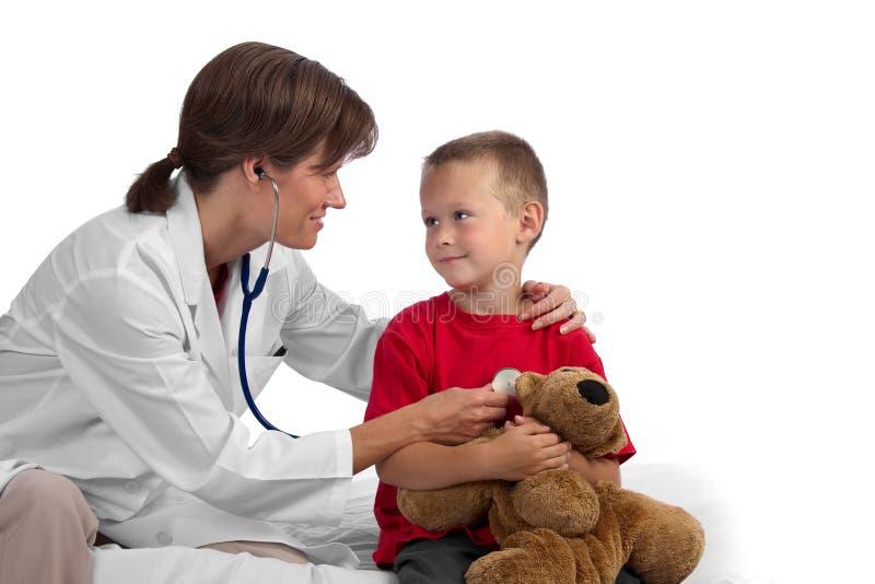 Medico caucasico femminile che dà ad un ragazzo una visita medica fotografia stock