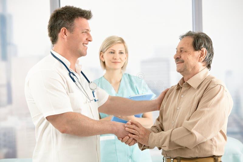 Medico che agita le mani con il paziente maggiore fotografia stock