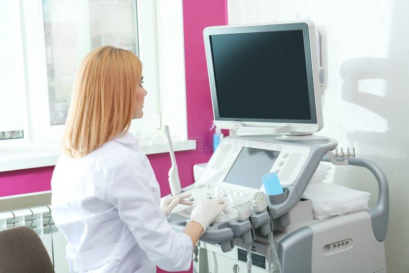 Medico che analizza i risultati di sistema diagnostico di ultrasuono in posto di lavoro fotografie stock libere da diritti