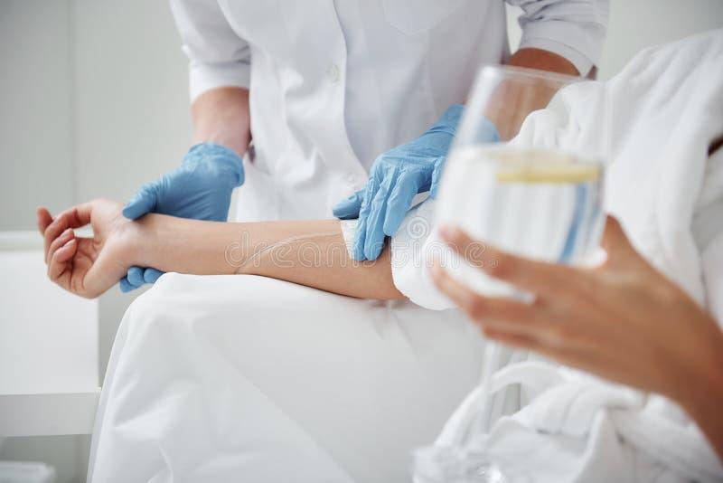Medico che attacca gocciolamento endovenoso sulla mano di signora fotografie stock libere da diritti