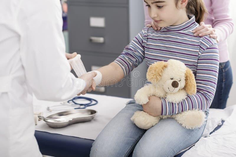 Medico che avvolge una fasciatura sul polso di una ragazza immagine stock