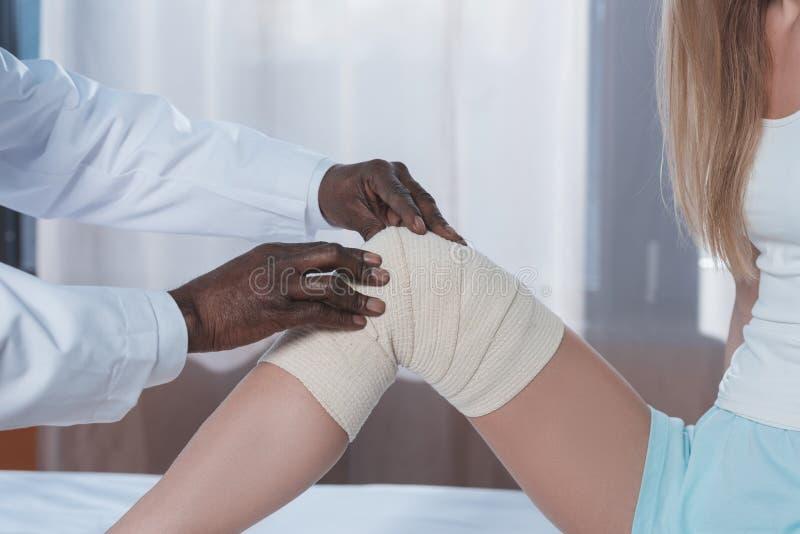 medico che benda ginocchio paziente immagine stock libera da diritti