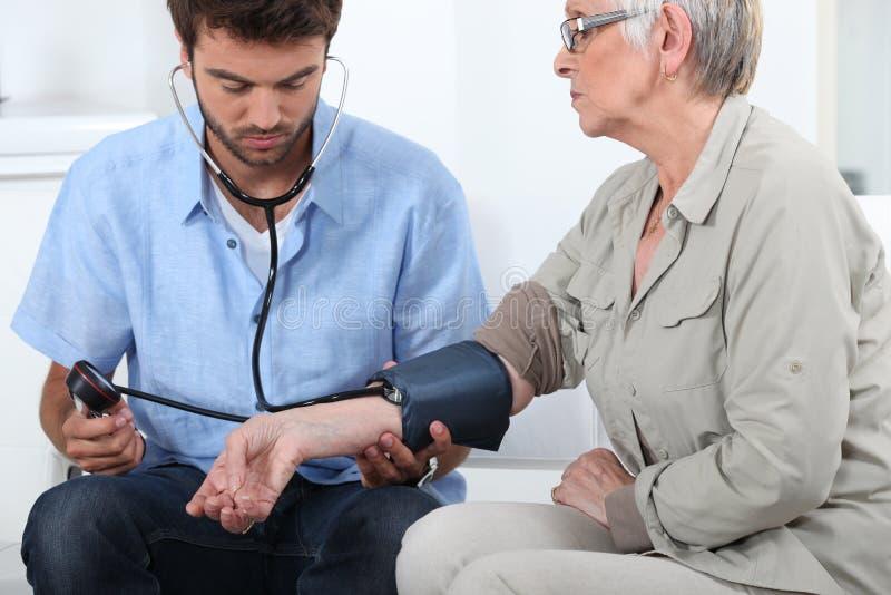 Medico che cattura la pressione sanguigna immagini stock
