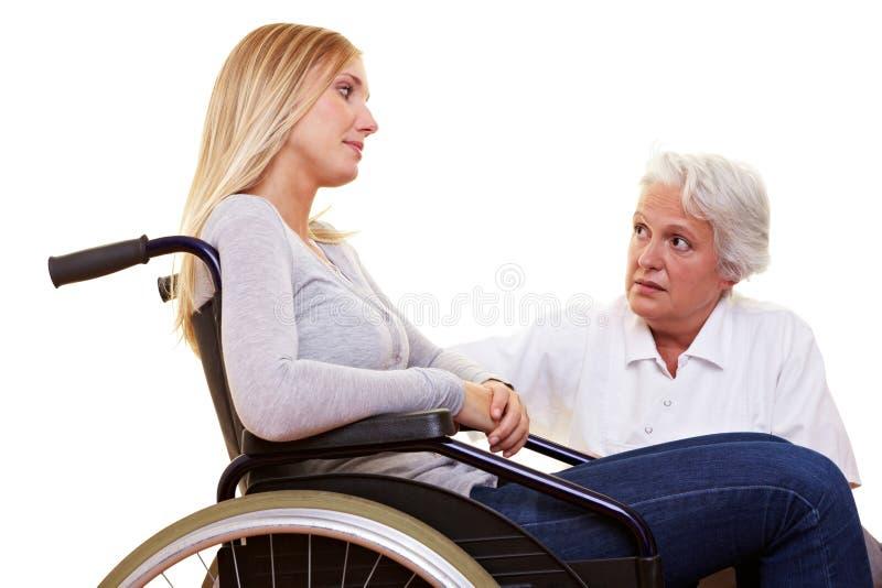 Medico che comunica con paziente invalido immagini stock