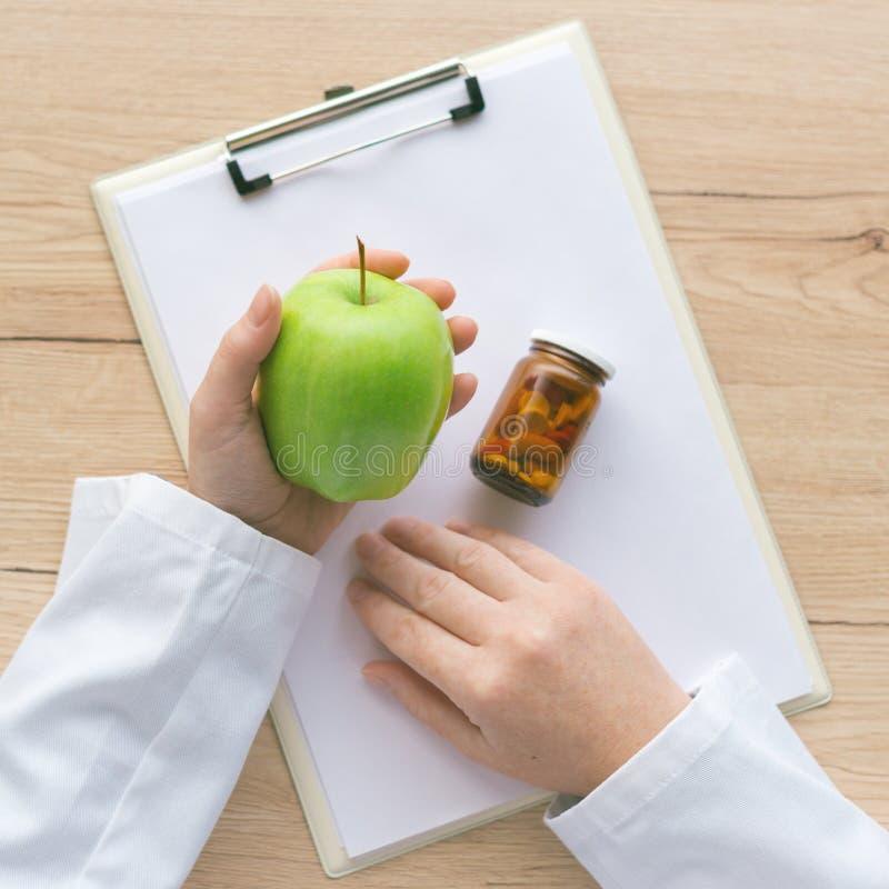 Medico che consiglia mela invece delle pillole e degli antibiotici immagini stock