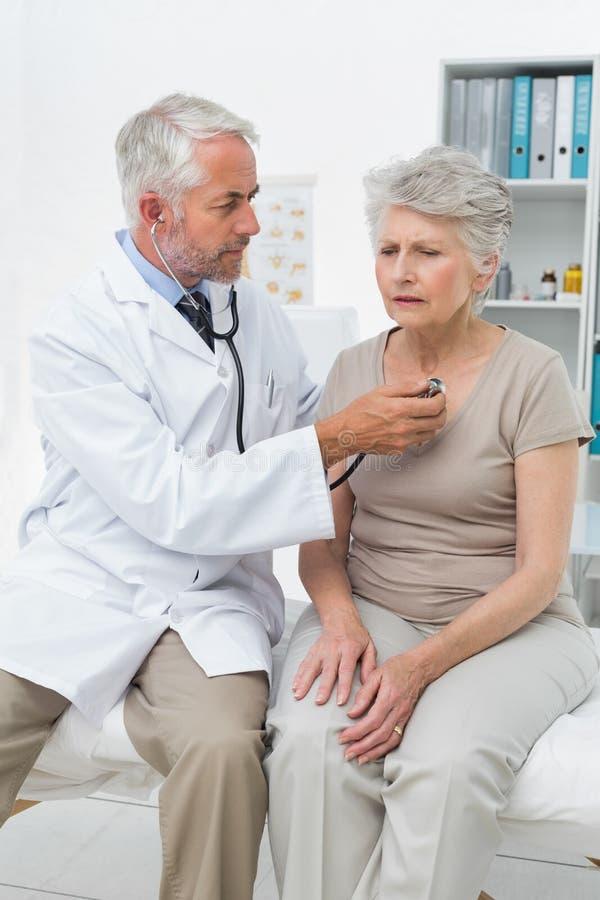Medico che controlla battito cardiaco dei pazienti facendo uso dello stetoscopio immagini stock libere da diritti