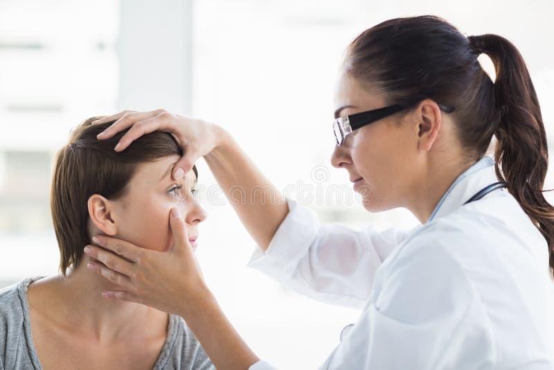 Medico che controlla l'occhio della donna fotografie stock