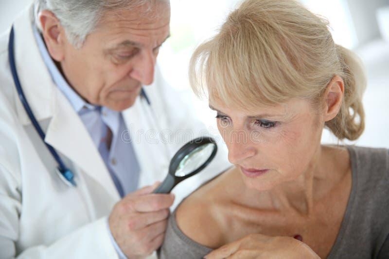 Medico che controlla la pelle della donna fotografia stock