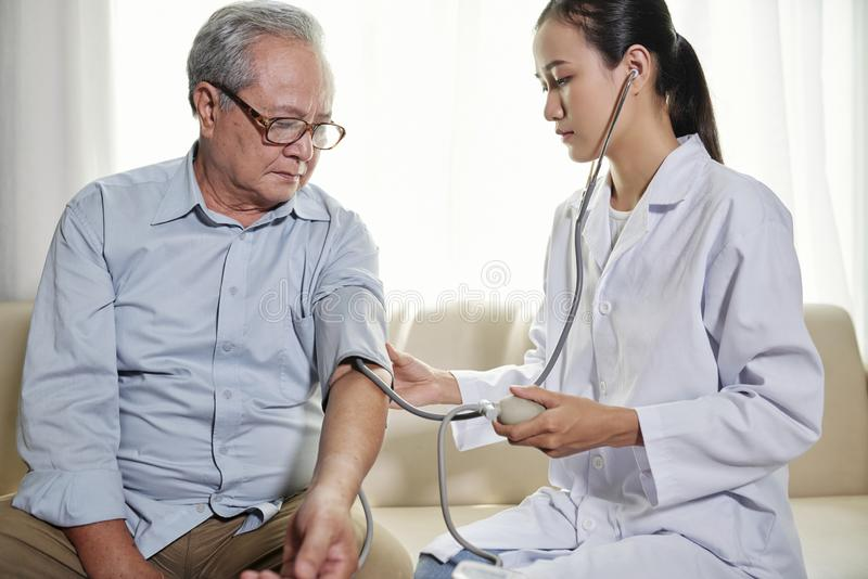 Medico che controlla pressione sanguigna del paziente immagini stock