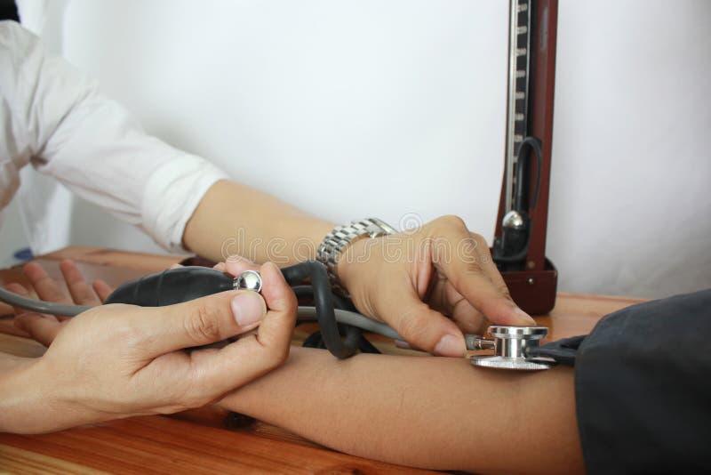 Medico che controlla pressione sanguigna di un paziente all'ospedale, concetto della medicina fotografia stock