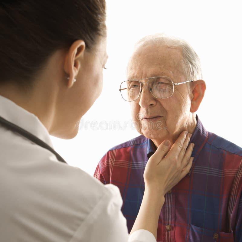 Medico che controlla un uomo anziano fotografia stock