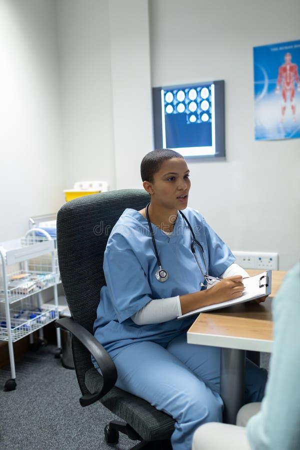 Medico che dà prescrizione alla donna incinta allo scrittorio fotografie stock