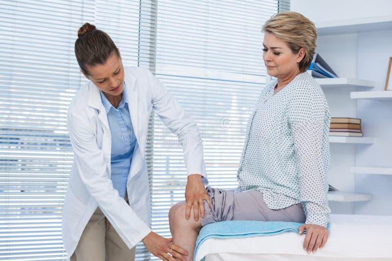 Medico che esamina ginocchio paziente fotografie stock