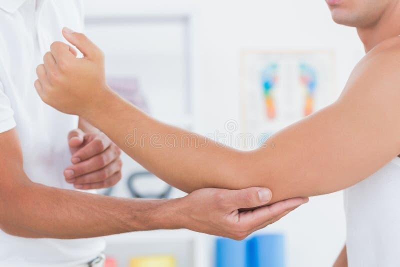 Medico che esamina il suo braccio paziente immagine stock libera da diritti