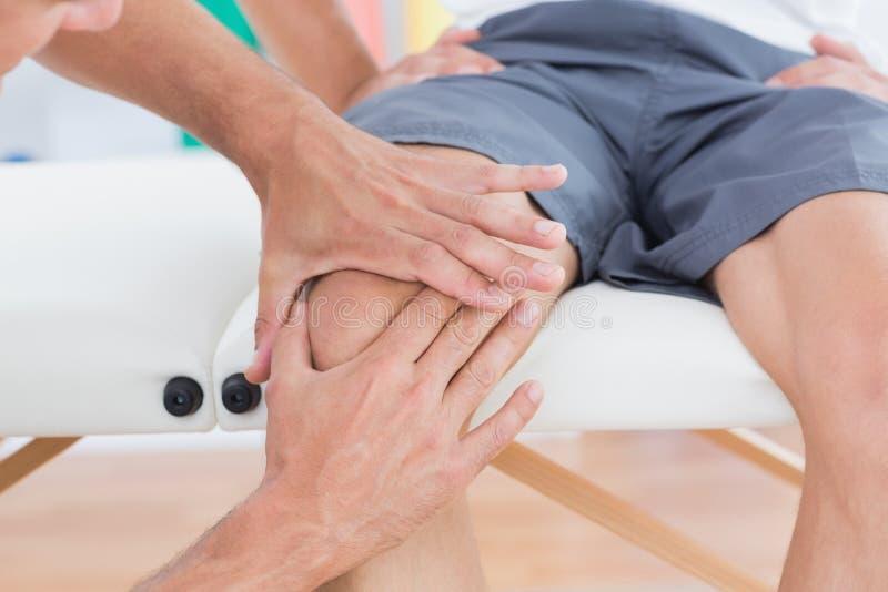 Medico che esamina il suo ginocchio paziente immagine stock