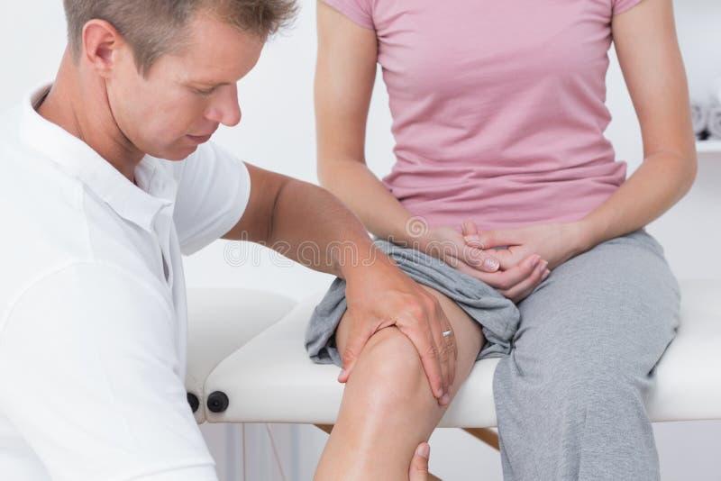 Medico che esamina il suo ginocchio paziente fotografie stock libere da diritti