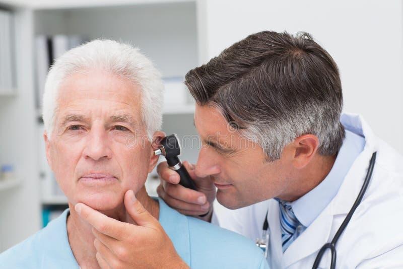 Medico che esamina l'orecchio senior dei pazienti con l'otoscopio immagini stock