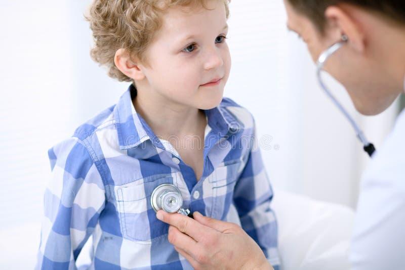Medico che esamina un paziente del bambino secondo lo stetoscopio immagini stock