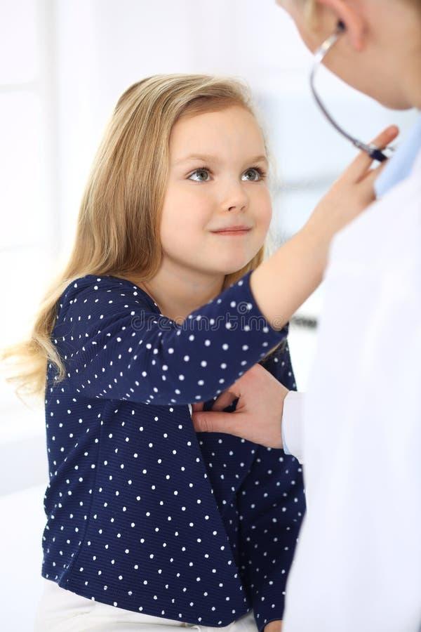 Medico che esamina un paziente del bambino secondo lo stetoscopio Neonata sveglia all'appuntamento del medico Concetto della medi immagine stock