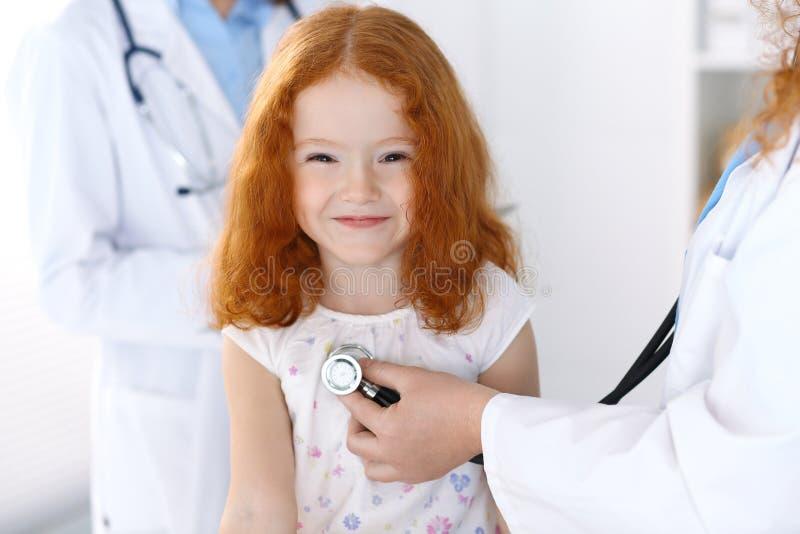 Medico che esamina una bambina con lo stetoscopio Concetto di sanità e della medicina fotografie stock