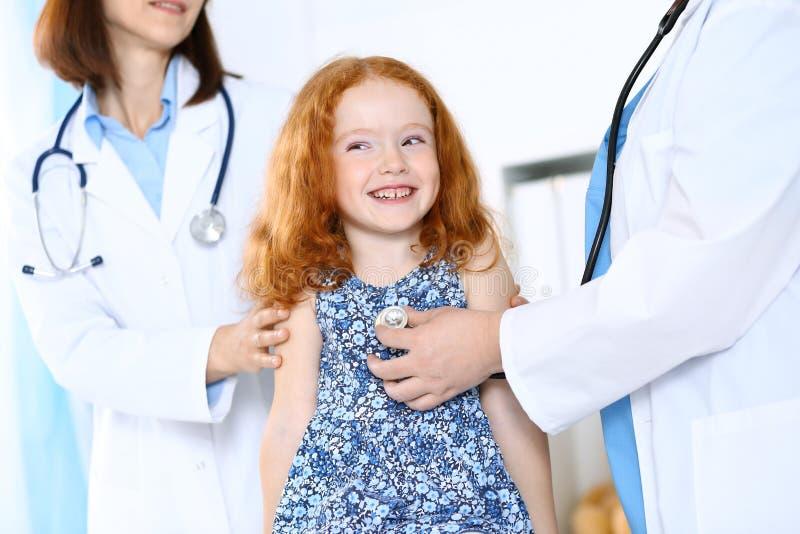 Medico che esamina una bambina con lo stetoscopio Concetto di sanità e della medicina fotografia stock